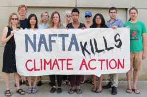 Climate activists with banner: NAFTA kills climate action